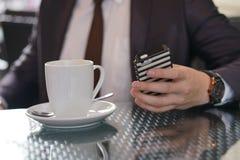 Uomo d'affari che si siede con una tazza di caffè e un telefono ad una tavola nera con una riflessione immagine stock