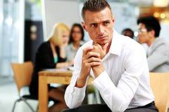 Uomo d'affari che si siede davanti ai colleghi Fotografie Stock Libere da Diritti