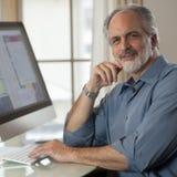 Uomo d'affari che si siede davanti al calcolatore Fotografia Stock Libera da Diritti