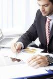 Uomo d'affari che si siede davanti al computer portatile Fotografia Stock