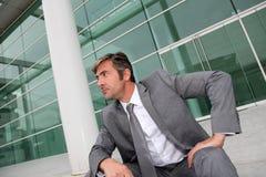 Uomo d'affari che si siede davanti alla costruzione moderna Immagini Stock Libere da Diritti