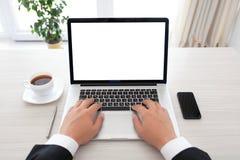Uomo d'affari che si siede dietro un computer portatile con lo schermo isolato Immagine Stock