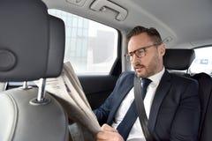 Uomo d'affari che si siede in giornale della lettura dell'automobile Fotografie Stock Libere da Diritti