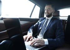 Uomo d'affari che si siede nel sedile posteriore di un'automobile, facendo uso del suo computer portatile Fotografie Stock