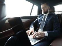 Uomo d'affari che si siede nel sedile posteriore di un'automobile, facendo uso del suo computer portatile Fotografia Stock