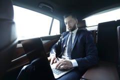 Uomo d'affari che si siede nel sedile posteriore di un'automobile, facendo uso del suo computer portatile Immagine Stock