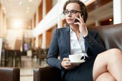 Uomo d'affari che si siede nell'ingresso dell'hotel facendo uso del telefono cellulare e del computer portatile Fotografie Stock Libere da Diritti