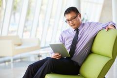 Uomo d'affari che si siede nell'ufficio moderno facendo uso della compressa di Digital Fotografie Stock