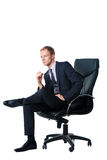 Uomo d'affari che si siede nella presidenza nera dell'ufficio fotografie stock