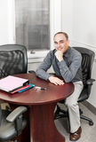 Uomo d'affari che si siede nella sala riunioni dell'ufficio fotografie stock