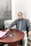 Uomo d'affari che si siede nella sala riunioni dell'ufficio fotografia stock
