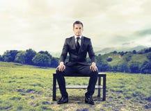 Uomo d'affari che si siede su un banco Fotografia Stock Libera da Diritti