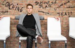 Uomo d'affari che si siede su una sedia dell'ufficio Fotografie Stock Libere da Diritti