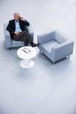 Uomo d'affari che si siede su una sedia e che parla sul telefono cellulare Immagini Stock Libere da Diritti
