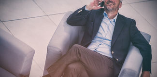 Uomo d'affari che si siede su una sedia e che parla sul telefono cellulare Immagine Stock Libera da Diritti