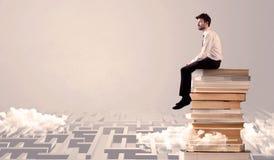 Uomo d'affari che si siede sui libri nel labirynth Fotografia Stock Libera da Diritti