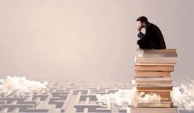 Uomo d'affari che si siede sui libri nel labirynth Fotografia Stock