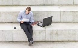 Uomo d'affari che si siede sui punti e che lavora con il computer. Immagini Stock Libere da Diritti