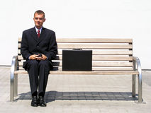 Uomo d'affari che si siede sul banco Fotografia Stock