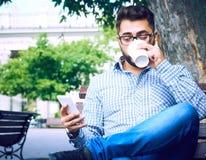 Uomo d'affari che si siede sul banco di parco con caffè facendo uso del telefono cellulare fotografia stock
