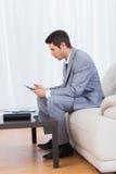 Uomo d'affari che si siede sul messaggio mandante un sms del sofà con il suo cellulare Immagini Stock