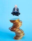 Uomo d'affari che si siede sul mucchio di soldi Fotografia Stock