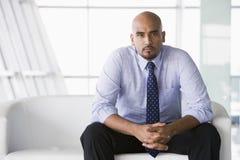 Uomo d'affari che si siede sul sofà in ingresso Immagine Stock Libera da Diritti