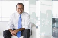 Uomo d'affari che si siede sul sofà in ingresso Fotografia Stock Libera da Diritti