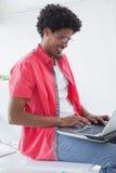 Uomo d'affari che si siede sul suo scrittorio facendo uso del computer portatile Immagini Stock