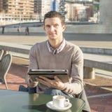 Uomo d'affari che si siede sulla barra del terrazzo con i tum della tazza e del computer portatile di caffè Fotografia Stock Libera da Diritti