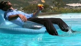 Uomo d'affari che si siede sulla boa mentre bevendo cocktail stock footage