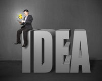 Uomo d'affari che si siede sulla cima della parola 3D Fotografia Stock Libera da Diritti