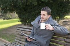 Uomo d'affari che si siede sulla linguetta di legno del computer portatile e del banco Immagine Stock Libera da Diritti