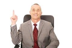 Uomo d'affari che si siede sulla poltrona e che indica su Fotografie Stock Libere da Diritti