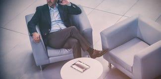 Uomo d'affari che si siede sulla sedia e che parla sul telefono cellulare Immagine Stock