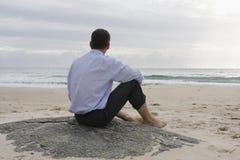 Uomo d'affari che si siede sulla spiaggia Immagine Stock Libera da Diritti