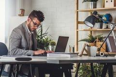 Uomo d'affari che si siede sulla sua scrivania che lavora ad un computer e che per mezzo del computer fotografia stock libera da diritti