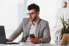 Uomo d'affari che si siede sulla sua scrivania che lavora ad un computer e che per mezzo del computer fotografie stock