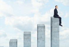 Uomo d'affari che si siede sulle più alte colonne concrete del grafico royalty illustrazione gratis