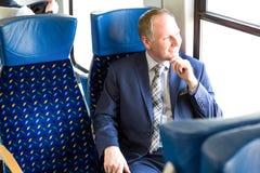 Uomo d'affari che si siede in un treno fotografie stock