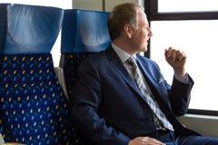Uomo d'affari che si siede in un treno immagini stock libere da diritti