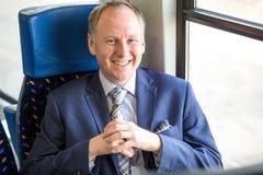 Uomo d'affari che si siede in un treno immagini stock