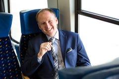 Uomo d'affari che si siede in un treno fotografia stock libera da diritti