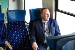 Uomo d'affari che si siede in un treno Immagine Stock