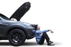 Uomo d'affari che si siede vicino all'automobile rotta immagine stock