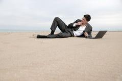 Uomo d'affari che si trova sulla spiaggia Fotografie Stock