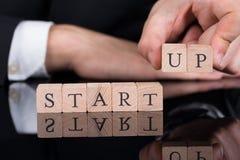 Uomo d'affari che sistema i blocchi startup sullo scrittorio Immagini Stock
