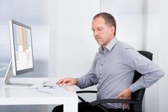 Uomo d'affari che soffre dal dolore alla schiena immagini stock