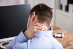 Uomo d'affari che soffre dal dolore del collo immagine stock