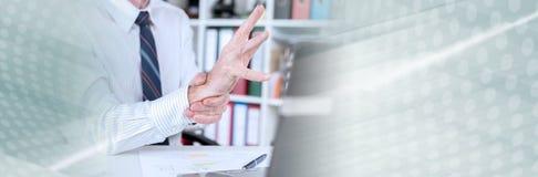 Uomo d'affari che soffre dal dolore del polso Bandiera panoramica fotografie stock libere da diritti